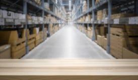 Holztischspitze vor großem unscharfem Inventarvorrat lizenzfreie stockfotografie