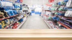 Holztischspitze vor unscharfer Hardware und Gemischtwarenladen stockbilder