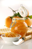 Homamade Orange jam. Bottle with homemade (real) orange jam, plate, knife and fresh oranges on back, soft focus Royalty Free Stock Images