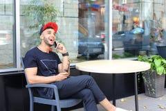 Hombre árabe del individuo confiado hermoso que habla en el teléfono, sonrisas y lau Foto de archivo libre de regalías