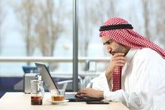 Hombre árabe del saudí preocupante con el ordenador portátil imagenes de archivo