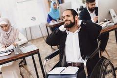 Hombre árabe discapacitado en la silla de ruedas que trabaja en oficina Daños del cuello del ` s del hombre imágenes de archivo libres de regalías