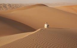 Hombre árabe en el equipo tradicional que se sienta en el desierto árabe y que disfruta del paisaje Fotografía de archivo libre de regalías