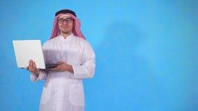 Hombre árabe en un fondo azul aislado con el ordenador portátil que mira la cámara almacen de metraje de vídeo