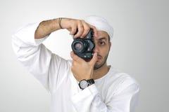 Hombre árabe joven que usa sosteniendo su cámara lista para tirar, aislado Fotografía de archivo libre de regalías