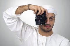 Hombre árabe joven que usa sosteniendo su cámara lista para tirar, aislado Imagen de archivo