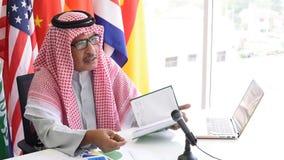 Hombre árabe o musulmán explicar sobre su negocio de aceite durante Conferencia Internacional almacen de video