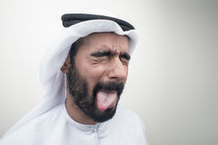 Hombre árabe que se pega hacia fuera la lengua, individuo árabe con el expr divertido Imagen de archivo