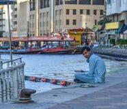 Hombre árabe que se sienta en el parque de Dubai Creek imagenes de archivo