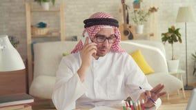Hombre árabe que se sienta en la tabla y que habla en un smartphone almacen de video