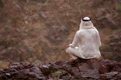Hombre árabe que se sienta en rocas Foto de archivo libre de regalías