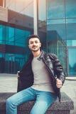 Hombre árabe que toma su capa apagado delante del edificio moderno El hombre joven muestra apagado Imagen de archivo