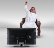 Hombre árabe que ve la TV y que reacciona Imagen de archivo libre de regalías