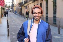 Hombre étnico fresco que sonríe en fondo urbano foto de archivo