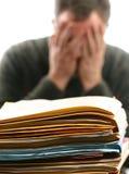 Hombre abrumado con el trabajo de oficina Fotografía de archivo libre de regalías