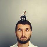Hombre absurdo con el pequeño hombre aburrido en la cabeza imagen de archivo libre de regalías