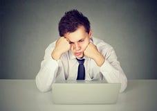 Hombre aburrido con exceso de trabajo que se sienta en el escritorio con el ordenador portátil que mira abajo Imagenes de archivo