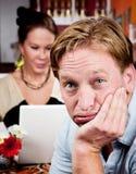 Hombre aburrido con la mujer en el ordenador portátil Fotos de archivo