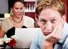 Hombre aburrido con la mujer en el ordenador portátil Imagen de archivo