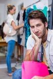 Hombre aburrido con los panieres que se sientan delante de su novia Foto de archivo libre de regalías