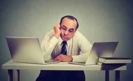 Hombre aburrido que se sienta delante de dos ordenadores portátiles imagenes de archivo
