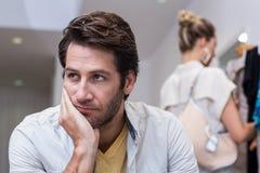 Hombre aburrido que se sienta delante de su novia Imagenes de archivo