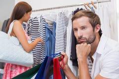 Hombre aburrido que se sienta y que espera delante de su mujer Imagen de archivo