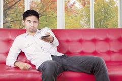 Hombre aburrido que ve la TV en casa Foto de archivo
