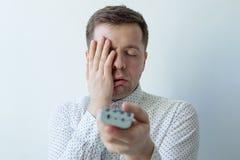 Hombre aburrido que ve la TV y zapping la cara cerrada con la mano Imagen de archivo