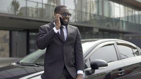 Hombre acertado en traje costoso que comunica en el teléfono, colocándose cerca de su coche almacen de video