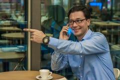 Hombre acertado joven hermoso que hace un gesto agradable Hombre de negocios de invitación Hola ` m de I aquí foto de archivo