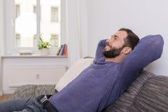 Hombre acertado que se relaja en el sofá en casa Imagenes de archivo