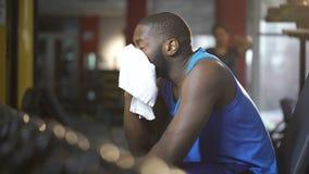 Hombre activo agotado después del entrenamiento en gimnasio, barrido sudado con la toalla, aptitud metrajes
