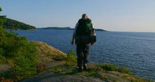 Hombre activo con la mochila que camina en el bosque por el mar en la puesta del sol metrajes