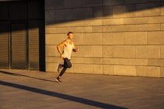 Hombre activo del gogger que corre en el d3ia en la ciudad urbana en el mornin fotografía de archivo