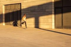 Hombre activo del gogger que corre en el d3ia en la ciudad urbana en el mornin foto de archivo