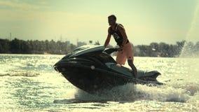 Hombre activo en el esquí del jet que se divierte en el río en la puesta del sol en la cámara lenta metrajes