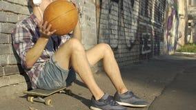Hombre activo que se sienta en el monopatín, jugando la bola y escuchando la música en auriculares metrajes