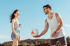 Hombre activo y mujer que juegan al voleibol en la playa junto imagen de archivo