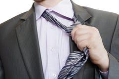Hombre adecuado que rasga de su lazo en el fondo blanco Imagen de archivo libre de regalías