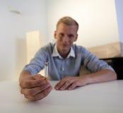 Hombre adicto que sostiene un cigarrillo Foto de archivo libre de regalías