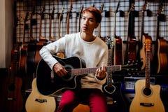 Hombre adolescente asiático hermoso que toca la guitarra en tienda de la guitarra Fotografía de archivo libre de regalías
