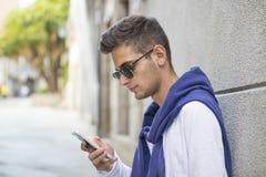 Hombre adolescente joven con el teléfono móvil Fotos de archivo
