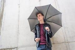 Hombre adolescente joven de Thougtful que se coloca en lluvia en ciudad con el paraguas Foto de archivo