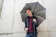 Hombre adolescente joven pensativo que se coloca en lluvia en ciudad con el paraguas Fotos de archivo libres de regalías