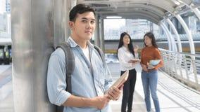 Hombre adolescente optimista enérgico con el soporte inmóvil y de libro para Fotografía de archivo