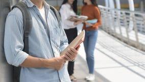 Hombre adolescente optimista enérgico con el soporte inmóvil y de libro para Imagenes de archivo