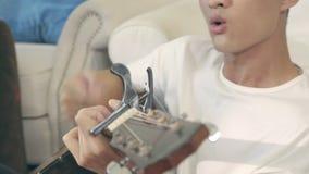Hombre adulto asiático joven que toca la guitarra almacen de metraje de vídeo