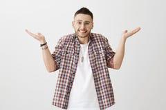 Hombre adulto atractivo avergonzado confuso con la cerda, vidrios transparentes que llevan, encogiendo con las palmas aumentadas Imagen de archivo libre de regalías
