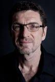 Hombre adulto atractivo con los vidrios en fondo negro Imágenes de archivo libres de regalías